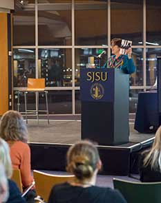 Photo of author on podium presenting published work