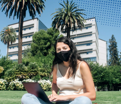 Student sitting outside with a laptop with a mask on.