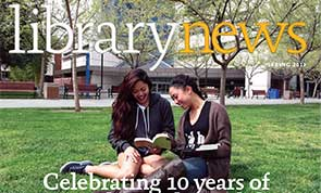 Photo of two students sitting on grass in front of the library building.