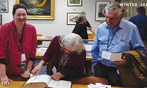 Photo of people in the library's special collections viewing a book from the collection.