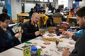 Photo of Eddy, Tabletop Game Group Leader, and other students playing games